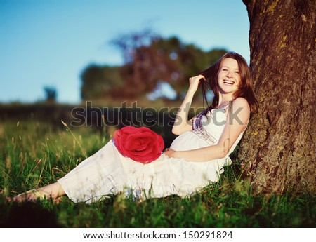 beautiful  pregnant woman  posing in garden, toothy smile - stock photo
