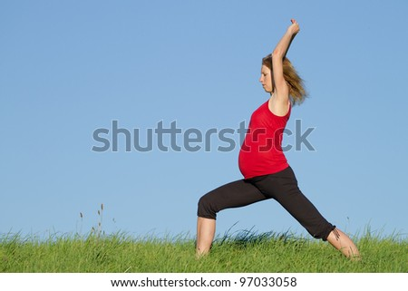 beautiful pregnant woman practicing yoga on a meadow