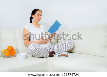 Beautiful pregnant woman reading book  on sofa at home - stock photo