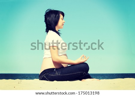Beautiful pregnant woman relaxing at the beach - stock photo
