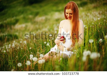 Beautiful pregnant woman relaxing in the park with apple