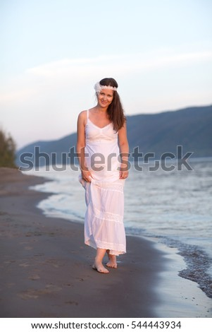 Beautiful pregnant woman relaxing on the beach in summer day