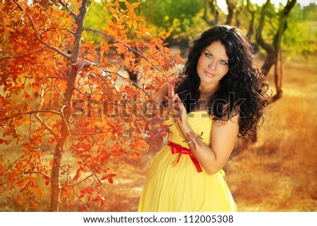 Beautiful pregnant woman relaxing outside in the park, autumn - stock photo