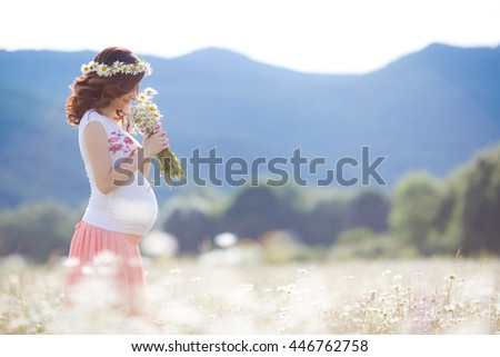 Beautiful pregnant woman resting in the chamomile field with bouquet of flowers. Close up of pregnant belly in nature. Happy pregnant woman portrait in chamomiles - stock photo