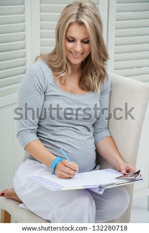 Beautiful pregnant woman sitting at home on chair, smiling and writing in pregnancy journal. Holding blue pencil and wearing blue watch. - stock photo