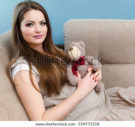 Beautiful pregnant woman sitting on the sofa and hold toy in hands - stock photo