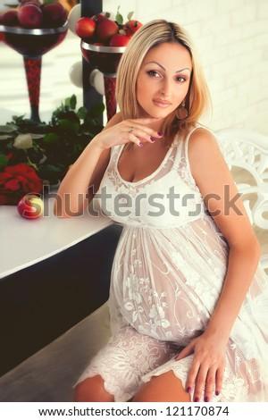 Beautiful pregnant woman smiling and looking at mirrow - stock photo