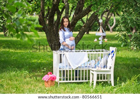Beautiful Pregnant woman standing by cradle in a garden - stock photo
