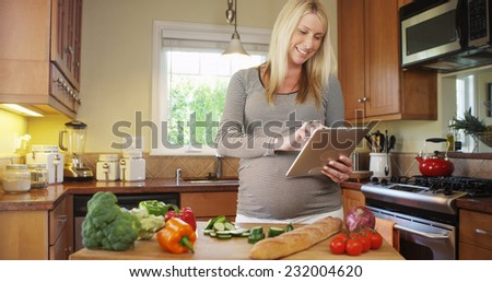 Beautiful pregnant woman using tablet in kitchen - stock photo