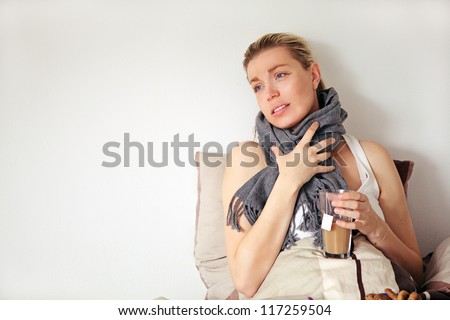 Beautiful pregnant woman with a pained expression sitting up against a pillow clutching a scarf around her neck suffering with seasonal flu - stock photo