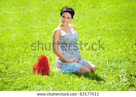 Beautiful pregnant woman with a red heart - stock photo