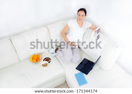 Beautiful pregnant woman with baby photos on sofa at home - stock photo