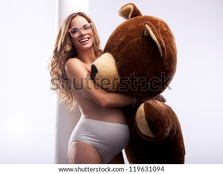 Beautiful pregnant woman with bear - stock photo