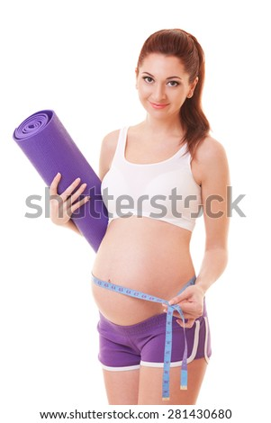 Beautiful pregnant woman with exercising mat and measure tape on the white background - stock photo