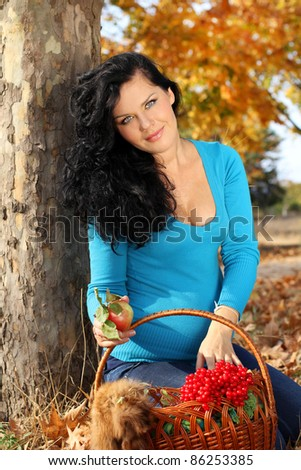 Beautiful pregnant woman with foodstuffs, autumn outdoors - stock photo