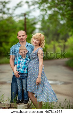 Beautiful pregnant woman with her husband and young son in green garden