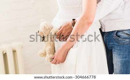 Beautiful pregnant woman with her husband in the room  - stock photo