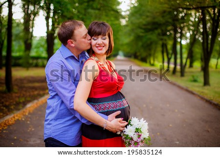 beautiful pregnant woman with her husband walks in the park. rest, relax