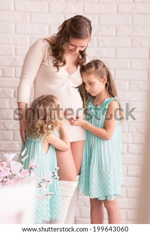 Beautiful pregnant woman with two daughters near the window - stock photo