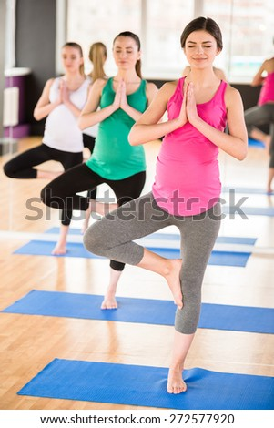 Beautiful pregnant women in yoga class standing in a fitness studio, doing exercise. - stock photo