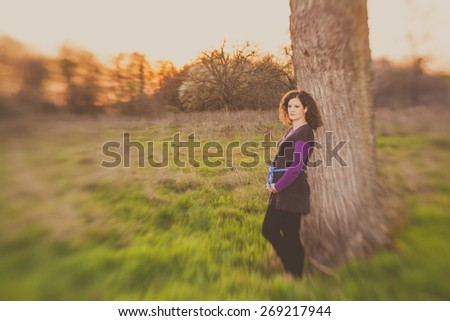 beautiful pregnant young woman outdoor taken by lensbaby for selective focus - stock photo