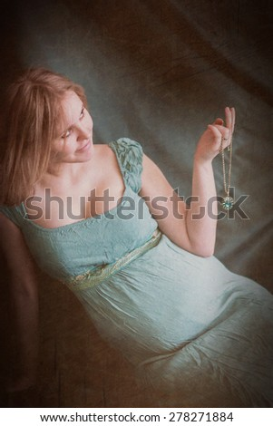 Beautiful pregnant young woman with pendant. Image with toning and aging effect - stock photo