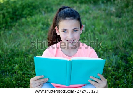 Beautiful preteen girl with blue eyes reading a book sitting on the grass - stock photo