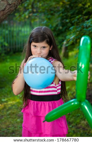 beautiful preteen girl with dark long hair playing with balloons - stock photo