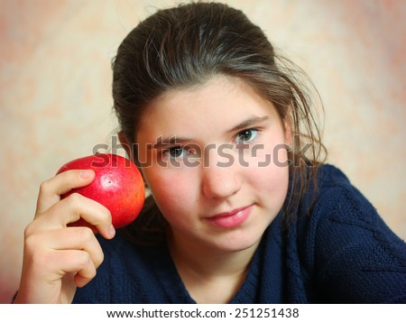 beautiful preteen girl with long dark hair close up portrait with apple - stock photo