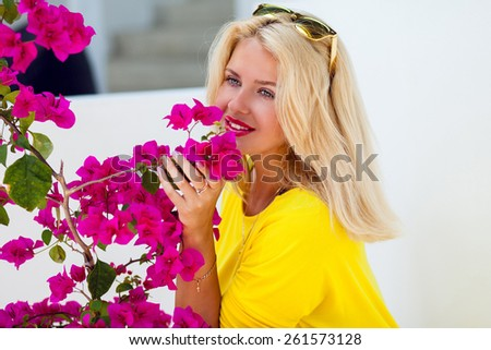 Beautiful  pretty  blonde lady with pink full lips posing near perfect flowers sniffs it  and enjoy their fragrance .Wearing sunglasses .  - stock photo