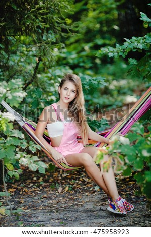 Beautiful pretty girl teenager young blond lying on a hammock in the woods in pink shorts. Summer. Holidays.
