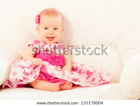 Beautiful pretty little baby girl in a pink dress sitting on the couch at home and smiling - stock photo