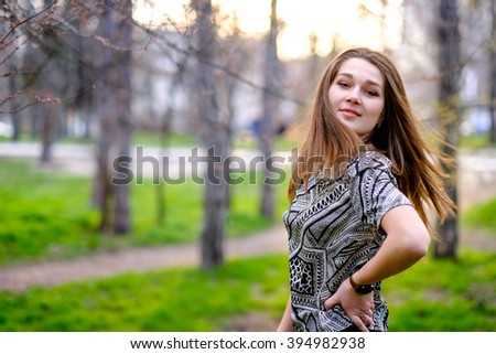 Beautiful, pretty student, teenage girl with long hair in the park on a sunny day. Portrait of a young attractive, smiling, happy woman outdoors. Summer, spring or autumn day outside on the nature. - stock photo