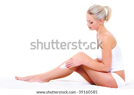 Beautiful pretty woman sitting on bed  applying moisturizer cream on her slim legs - stock photo