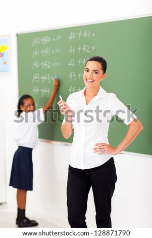 beautiful primary maths teacher in front of chalkboard in classroom - stock photo