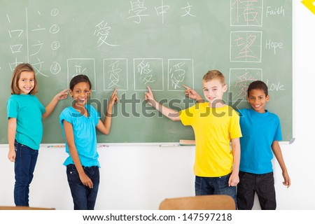 beautiful primary school students pointing their chinese writing work on blackboard - stock photo