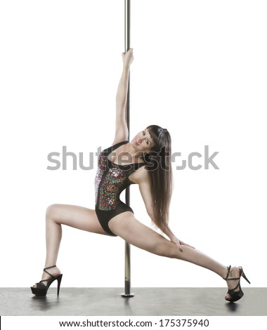 Beautiful professional dancer near the pole performs acrobatic element in gymnastic leotard. Performance ballet show. White background