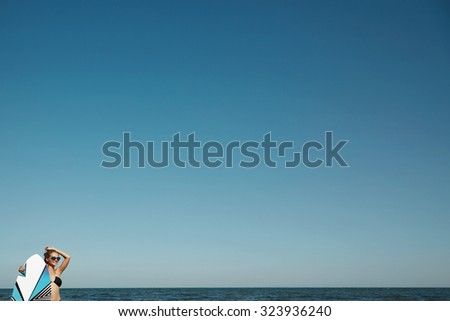 Beautiful professional surfer girl standing and relaxing after surfing sitting against  copy-space sky on background. - stock photo