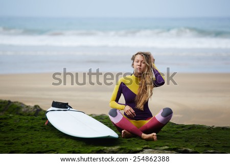 Beautiful professional surfer girl with long blond hair relaxing after surfing sitting against ocean with beautiful waves on background - stock photo