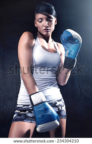 Beautiful professional woman boxing, looking at camera. - stock photo