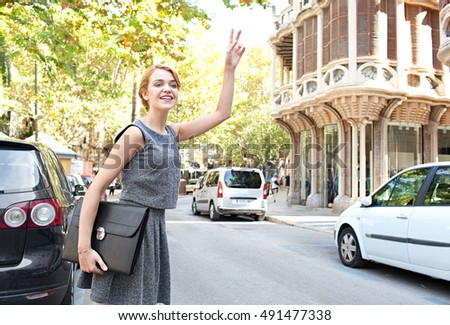 Beautiful professional woman calling a taxi in a classic street, smiling on a sunny day, outdoors road with traffic and stone buildings. Business woman in a rush, hitching a cab in financial city.
