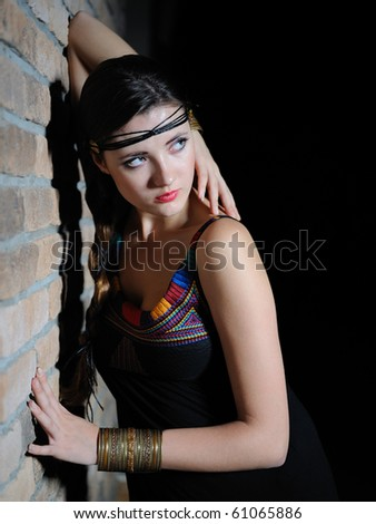 Beautiful pure  model woman with long healthy hair and pretty eye make-up near the wall - stock photo