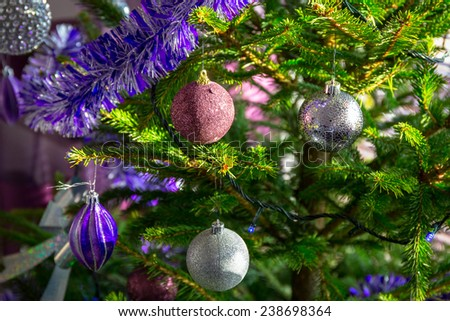 Beautiful purple and silver baubles on Christmas tree - stock photo