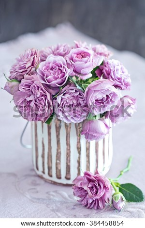 Beautiful purple rose flowers in a vase . - stock photo