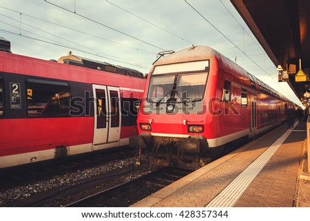 Beautiful railway station with modern red commuter train at colorful sunset in Nuremberg, Germany. Railroad with vintage toning - stock photo