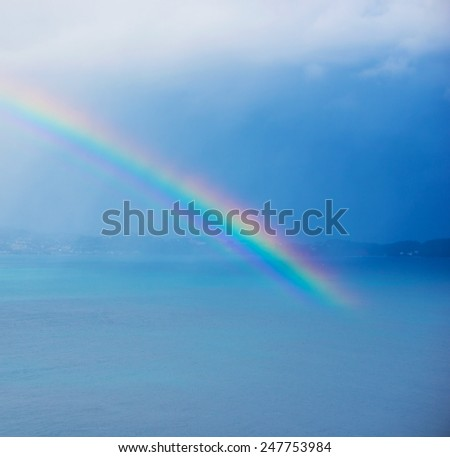 Beautiful rainbow over bay or ocean.  - stock photo