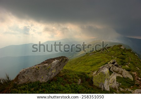 beautiful rays of light in the mountains after the storm - stock photo