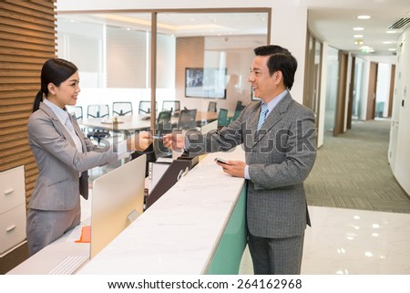 Beautiful receptionist giving smart card to the businessman - stock photo