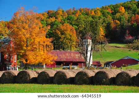 Beautiful red barn and fall colored trees on a gorgeous fall day - stock photo