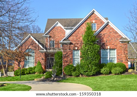 Beautiful Red Brick Suburban American Home with driveway - stock photo